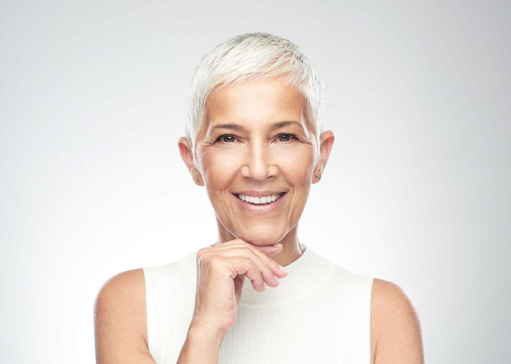 Eine hübsche ältere Dame mit gepflegter Haut lächelt in die Kamera.