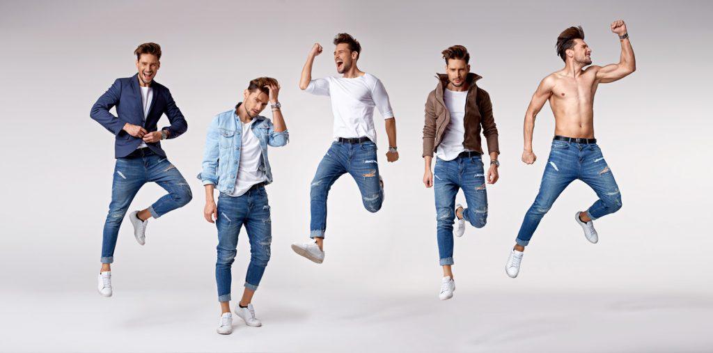 Junger Herr springt lebensfroh mit einer blauen Jeans in die Luft