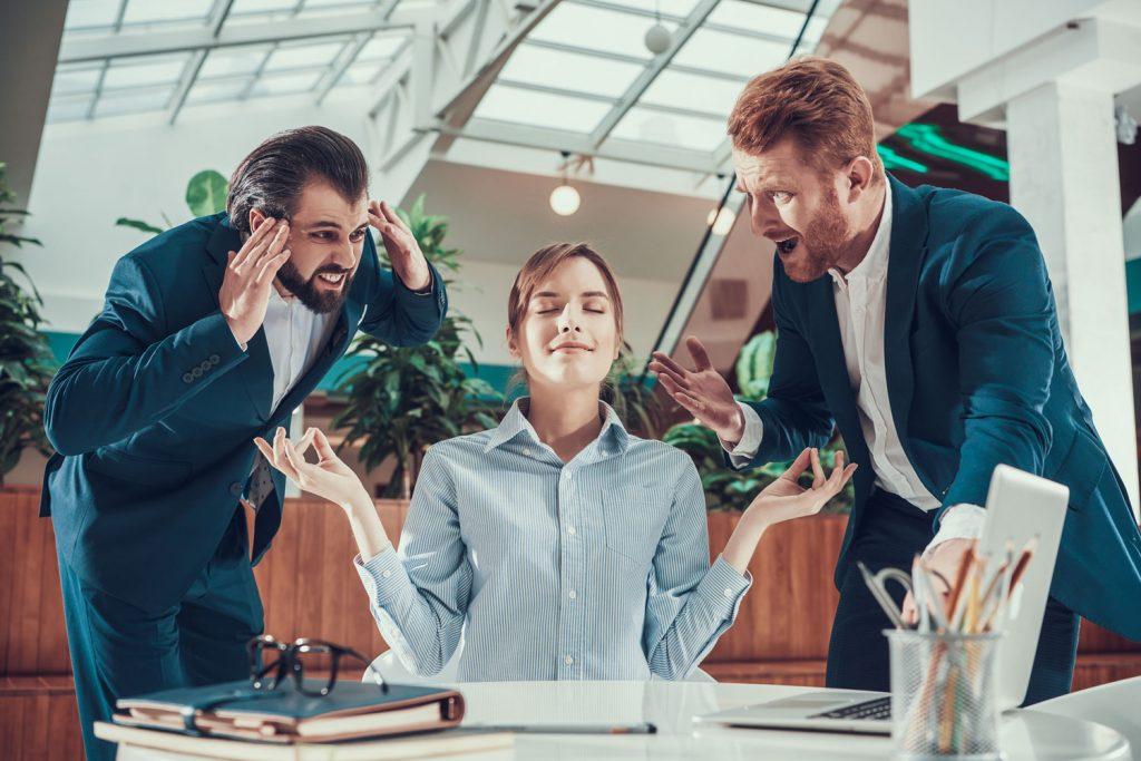 Meditierende hübsche Businessfrau wird von Männern angeschrieen.