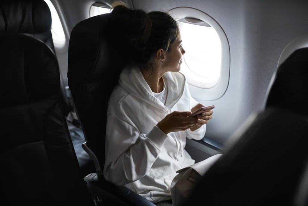 Junge Frau sitzt mit einem weißen Pullover im Flugzeug und hält ihr Smartphone in der Hand