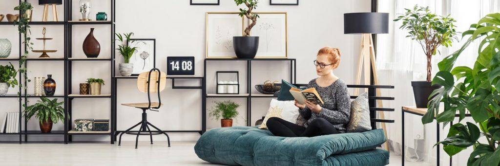 Hübsch eingerichtete Wohnung. Junge hübsche Frau, rothaarig, sitzt auf einem Sitzsack und liest ein Buch.