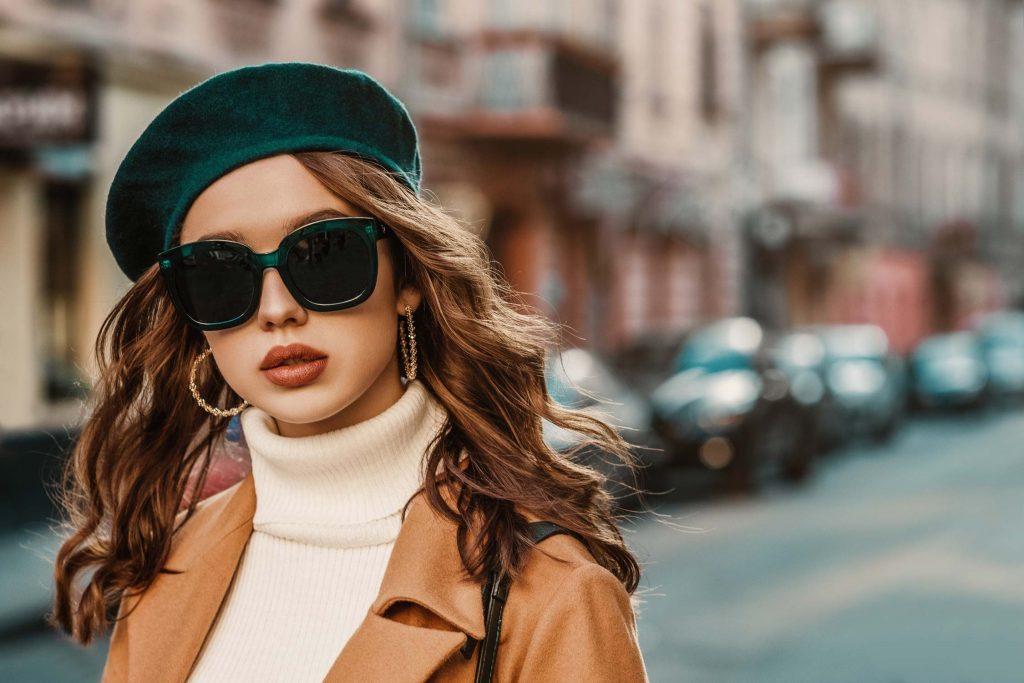 Junge brünette Dame mit stylischer Sonnenbrille und schickem Mantel