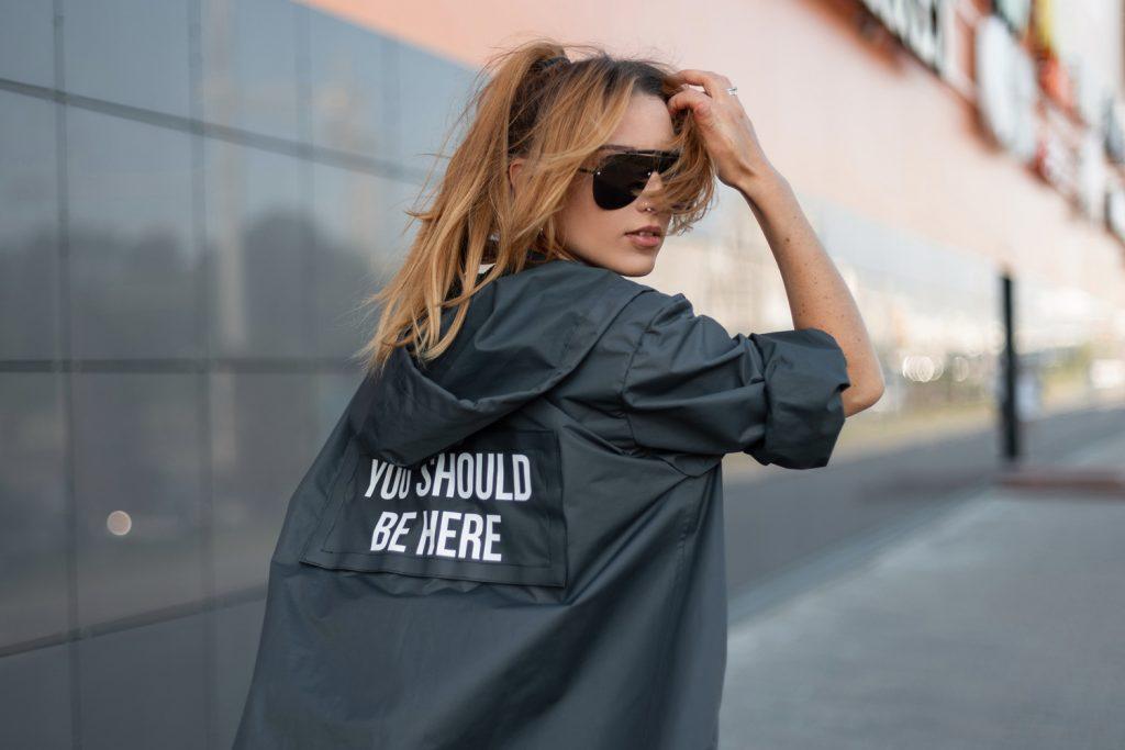 Junge Frau mit einer schwarzen runden Sonnenbrille und stylischer Jacke