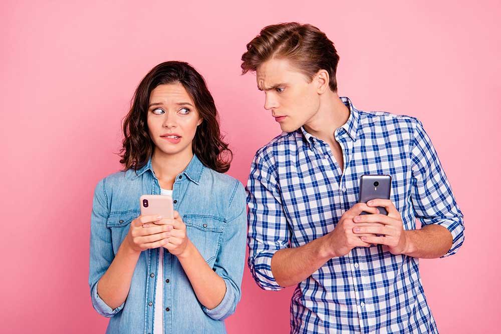 Ein Pärchen stehen vor einer Wand und er ertappt sie beim Fremdgehen und schaut auf ihr Smartphone.