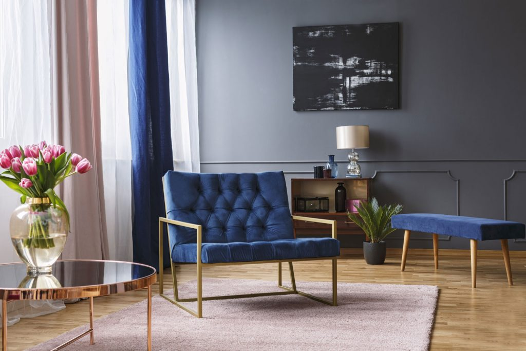Modern eingerichtetes Wohnzimmer mit einem dunkel blauen Sofa im Vordergrund