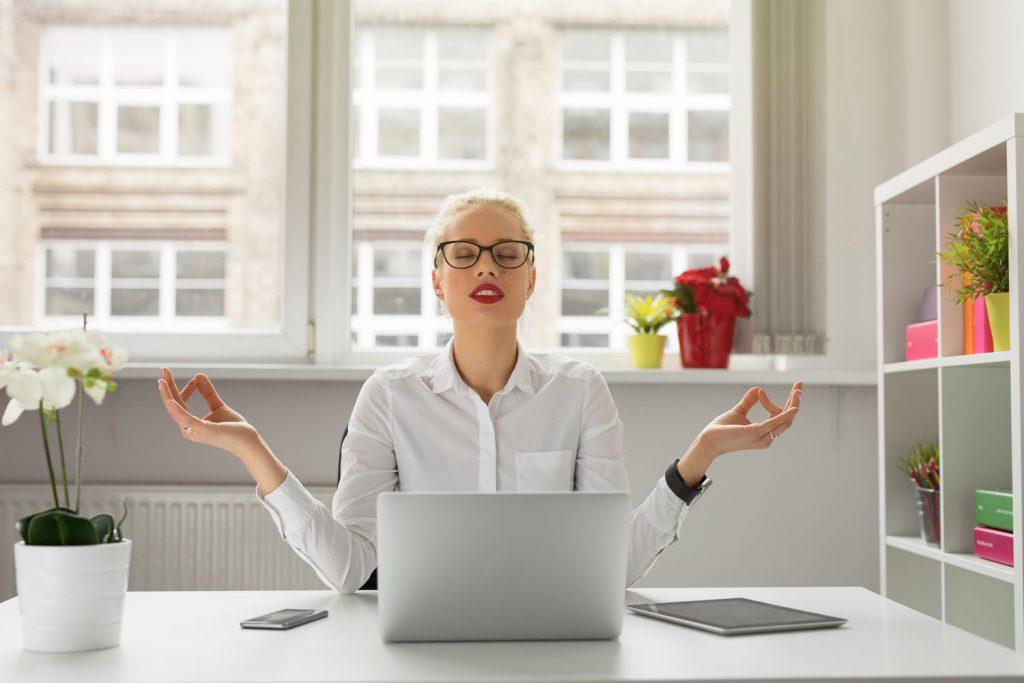 Hübsche Business Frau meditiert am Arbeitsplatz